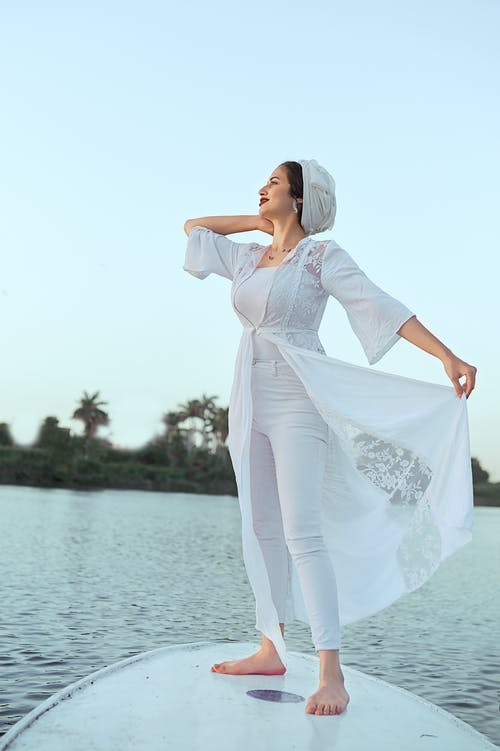 Woman in White Long Sleeve Dress Standing on Seashore