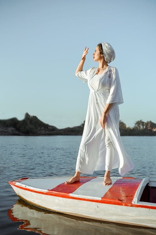 Woman in White Dress Standing on Red Surfboard