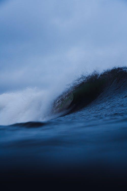 Foamy powerful wave rolling in stormy ocean under gray cloudy sky in daytime