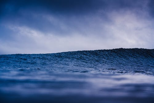 Water of majestic stormy ocean under cloudy sky