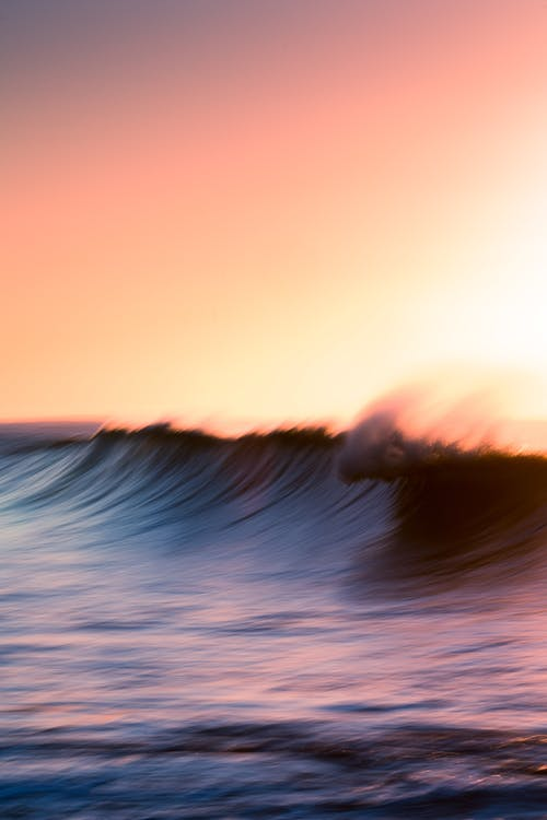 Spectacular majestic waves of powerful ocean under cloudless sky in bright orange sunset