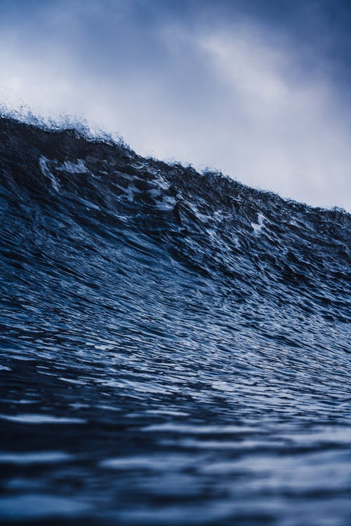 Water of powerful sea with massive waves under cloudy blue sky in daytime