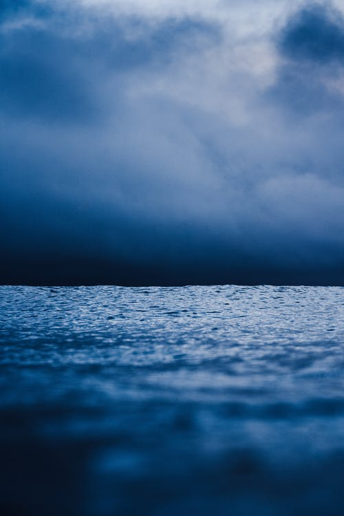 Calm water of rippling sea under cloudy sky