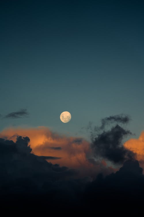 Glowing white moon with spots among cumulus gray cloudy in blue sky in evening