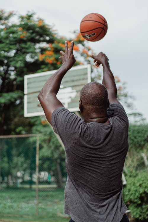 Man in Gray T-shirt Holding Basketball