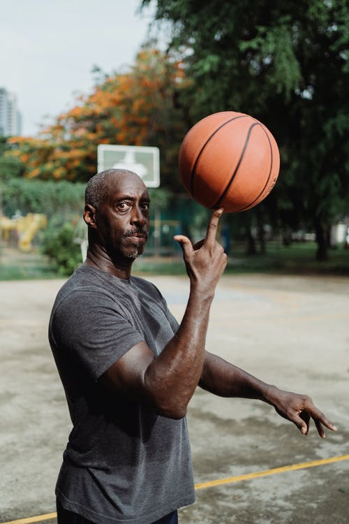 Man in Gray Crew Neck T-shirt Holding Basketball