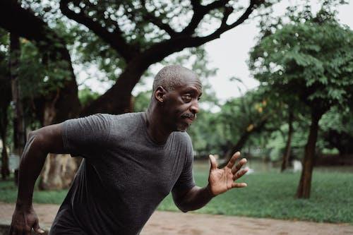 Man in Gray Crew Neck T-shirt Running