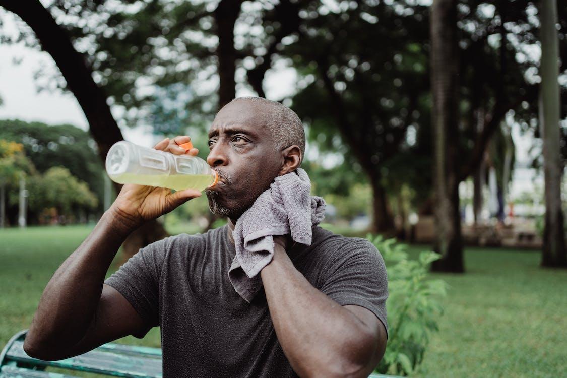 Man in Black Crew Neck T-shirt Drinking Yellow Liquid from Plastic Bottle