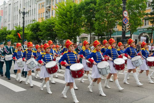 People in Blue and White Uniform Playing Drums