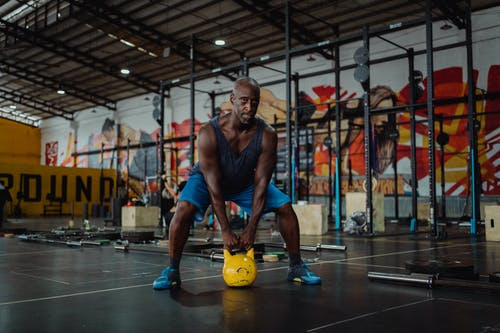 Man Using Yellow Kettlebell