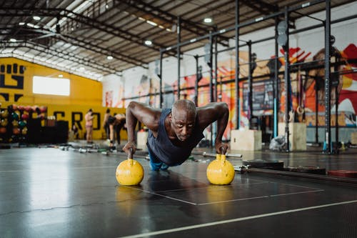 Photo of Man Doing Push-Ups Using Yellow Kettlebell