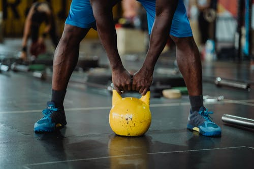 Person Using Yellow Kettlebell