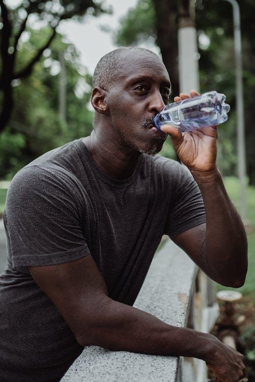 Man in Gray Crew Neck T-shirt Drinking Water