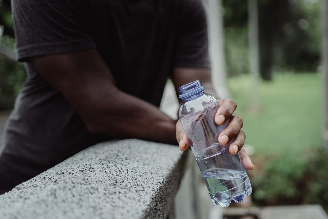Photo of Person Holding Clear Plastic Bottle