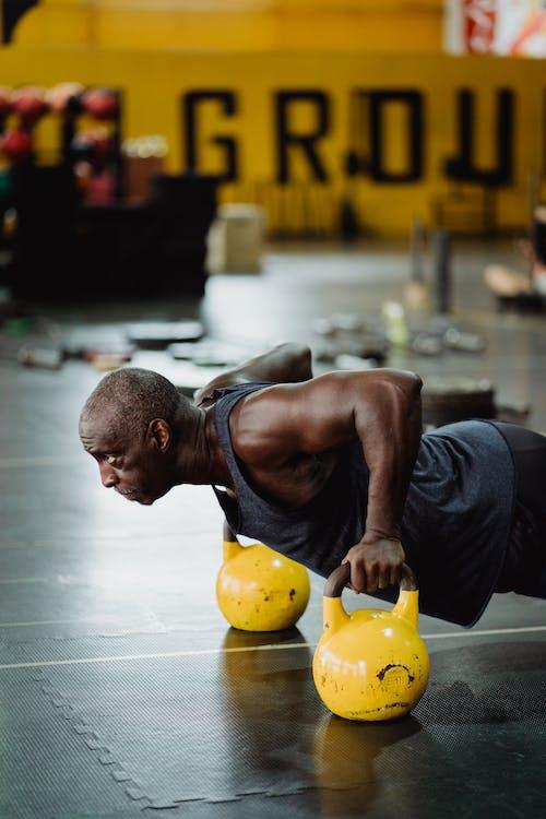 Photo of Man Doing Push-Ups Using Yellow Kettlebell