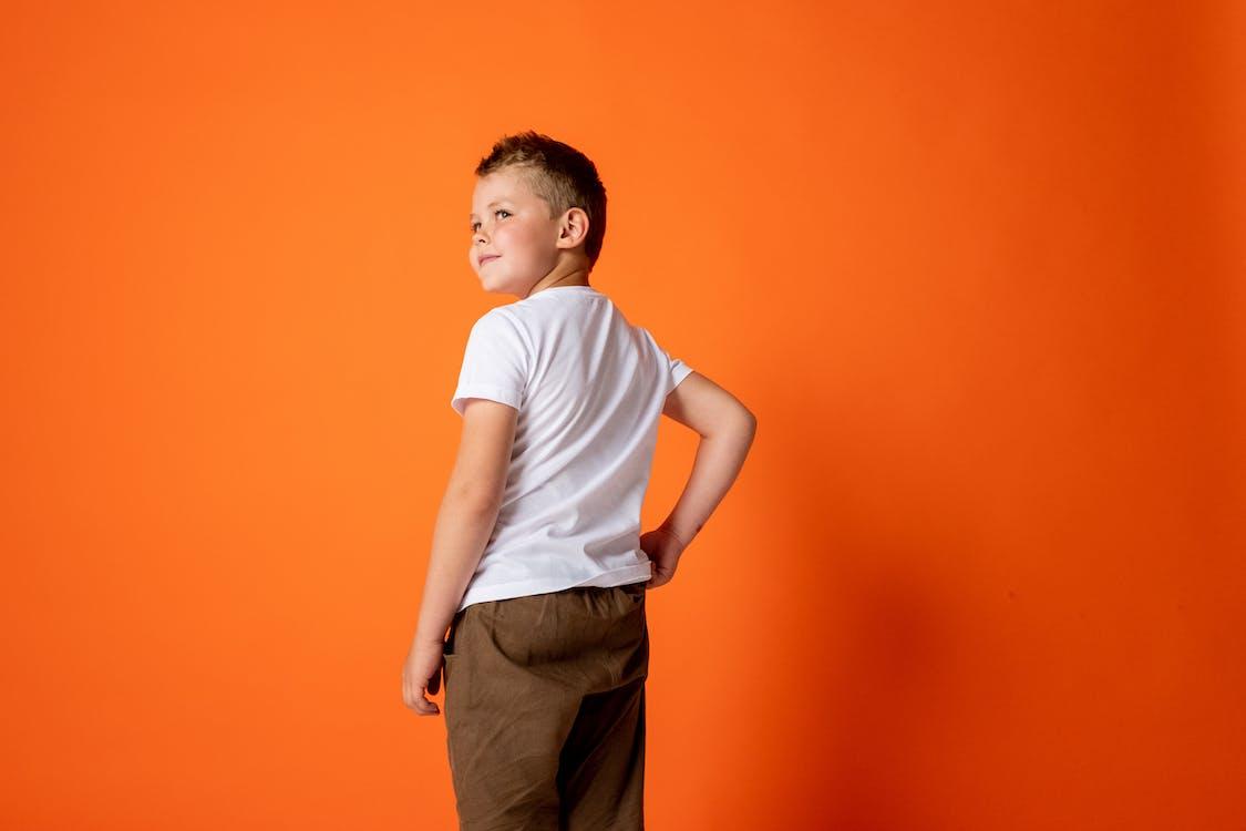 Jongen In Wit T Shirt Met Ronde Hals En Bruine Broek Tegen Een Oranje Achtergrond