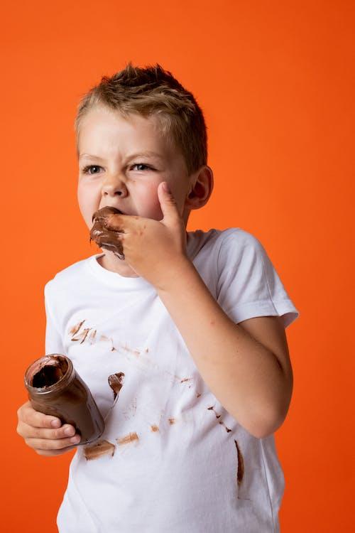 Boy in White Crew Neck T-shirt Holding Chocolate Jar