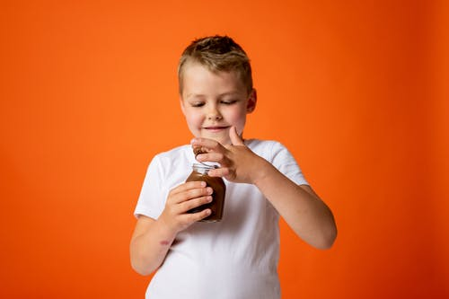 Boy in White Crew Neck T-shirt Holding Chocolate Jar
