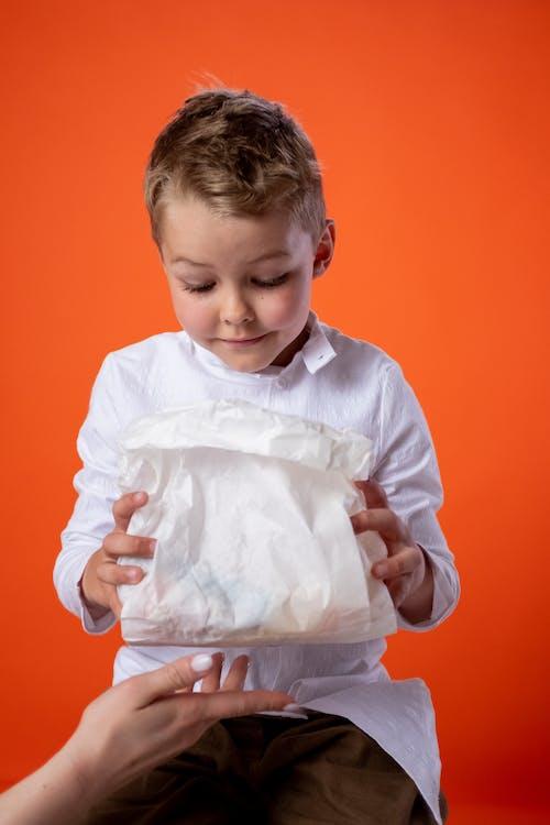 Boy in White Dress Shirt Holding White Paper