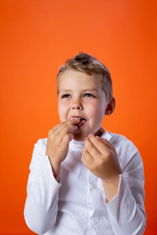 Boy in White Dress Shirt Eating