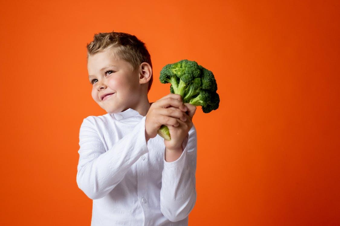 Boy in White Long Sleeve Shirt Holding Green Flower