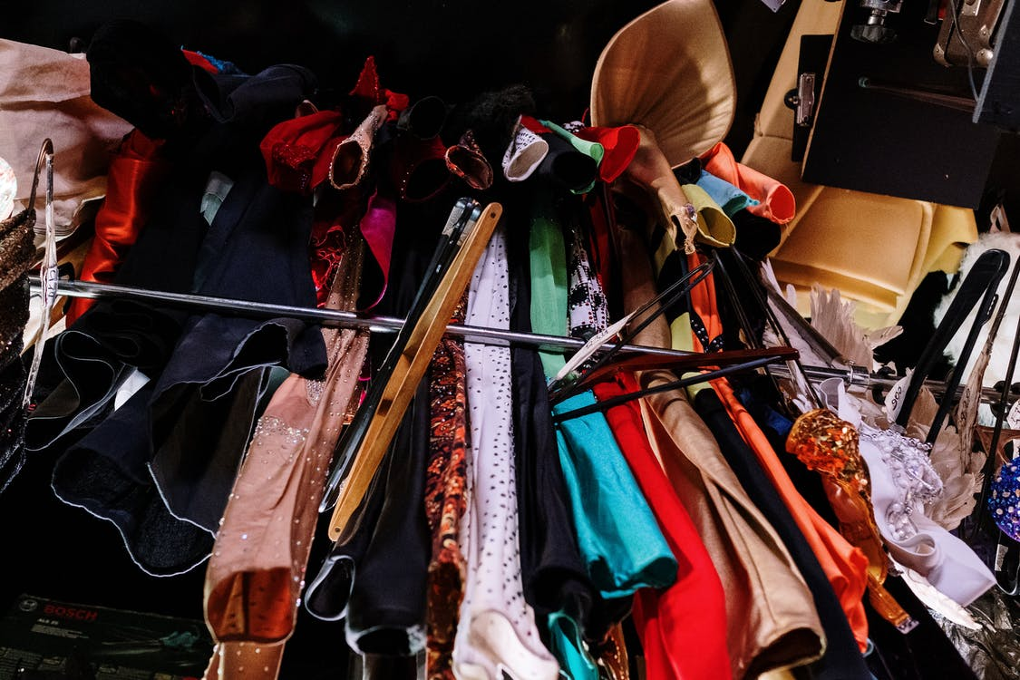 Assorted Clothes Hanged on Brown Wooden Rack
