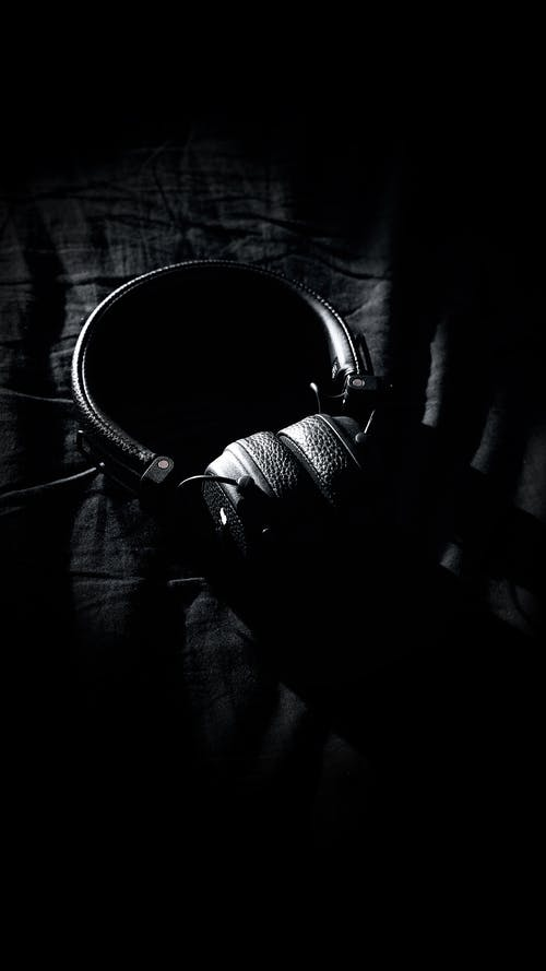 Black leather headphones on dark blanket
