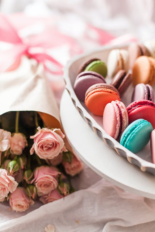 Macaroons next to bouquet of roses