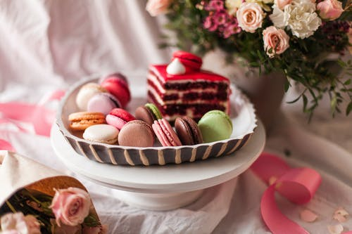 Stack of small round multi colored macaroons on saucer near cup of tea with piece of cake and bouquet of flowers in vase in bright room on blurred background