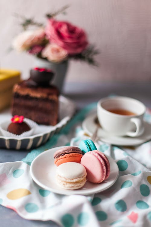 Overhead view of small round multi colored macaroons with cup of tea next to pink roses on table in bright cozy kitchen