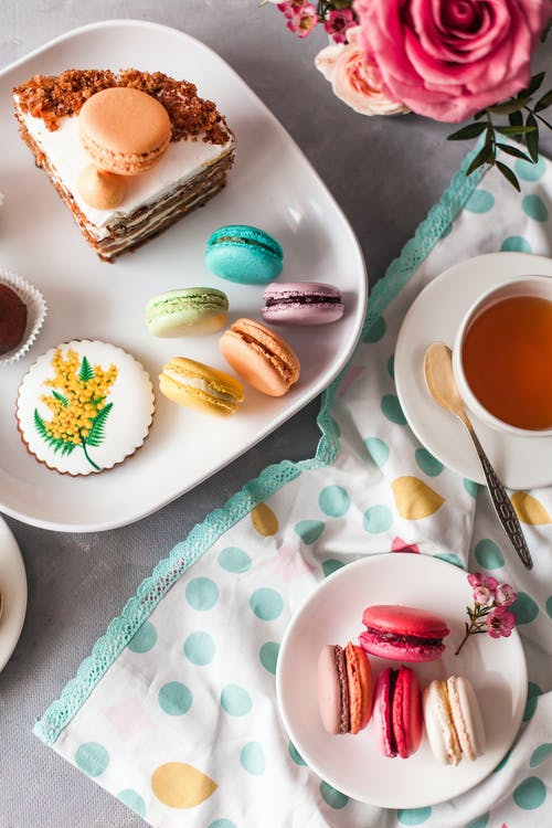 Macaroons and small cakes on table in cozy kitchen