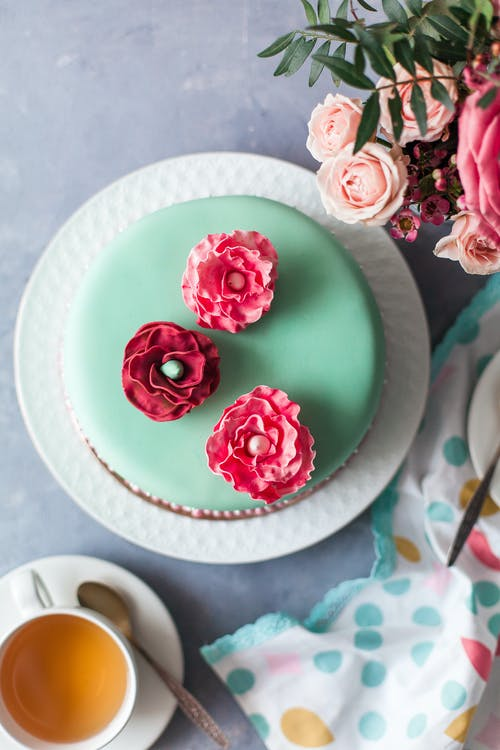Overhead view of round turquoise cake covered with edible flowers between cup of tea and bouquet of roses with dark green leaves on table in daylight