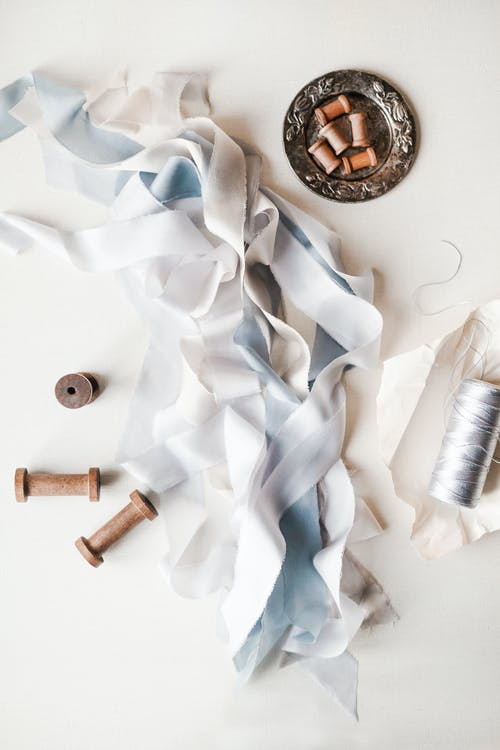Top view of white and light blue ribbons between simple empty spools on plate and spool of white threads in daylight on white background