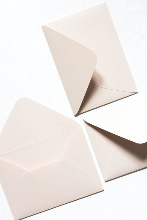 Overhead view of simple light beige unsealed envelops with triangular seal flap in light of lamps on white background