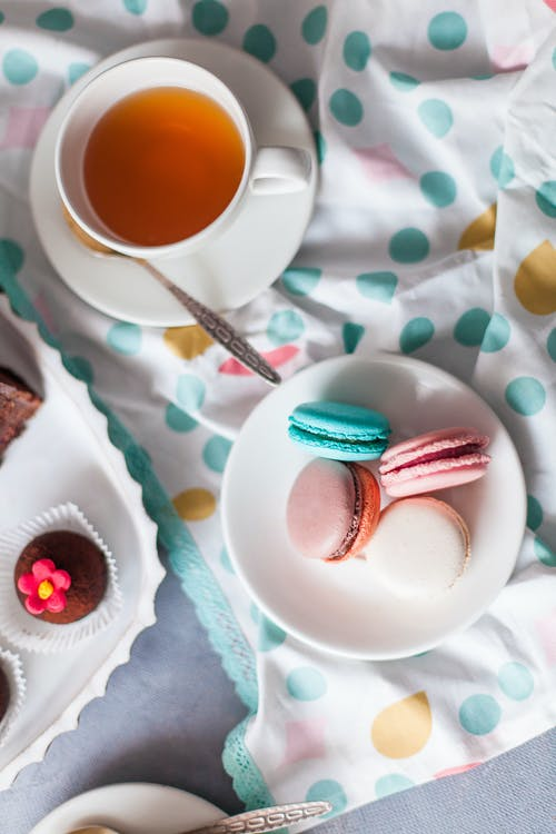 Cup of tea and desserts on table in bright room