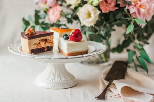 Pieces of cake on plate in room decorated with bouquet of flowers