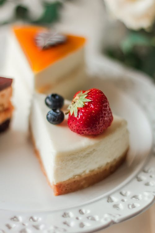 Delicious cheesecake with berries placed on white plate near pieces of other cakes