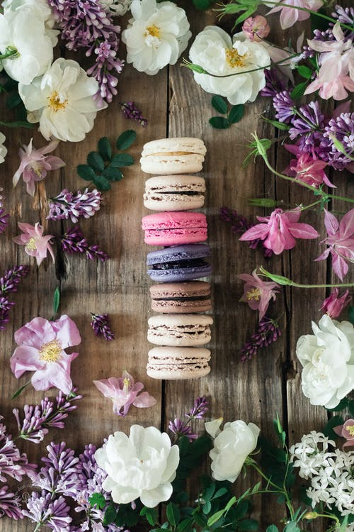 Top view of line of colorful macaroons placed on wooden table surrounded by flowers