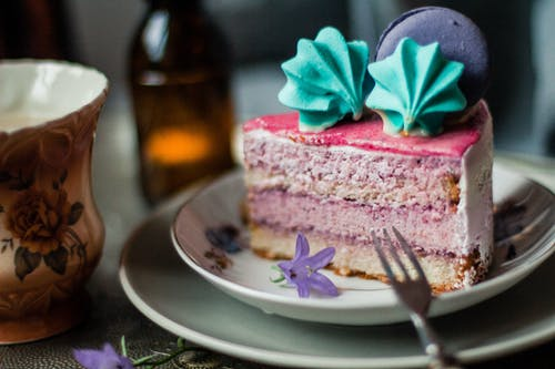 Piece of pink cake with meringues and macaron