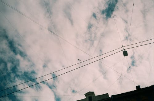 Black Coated Wire Under White Clouds