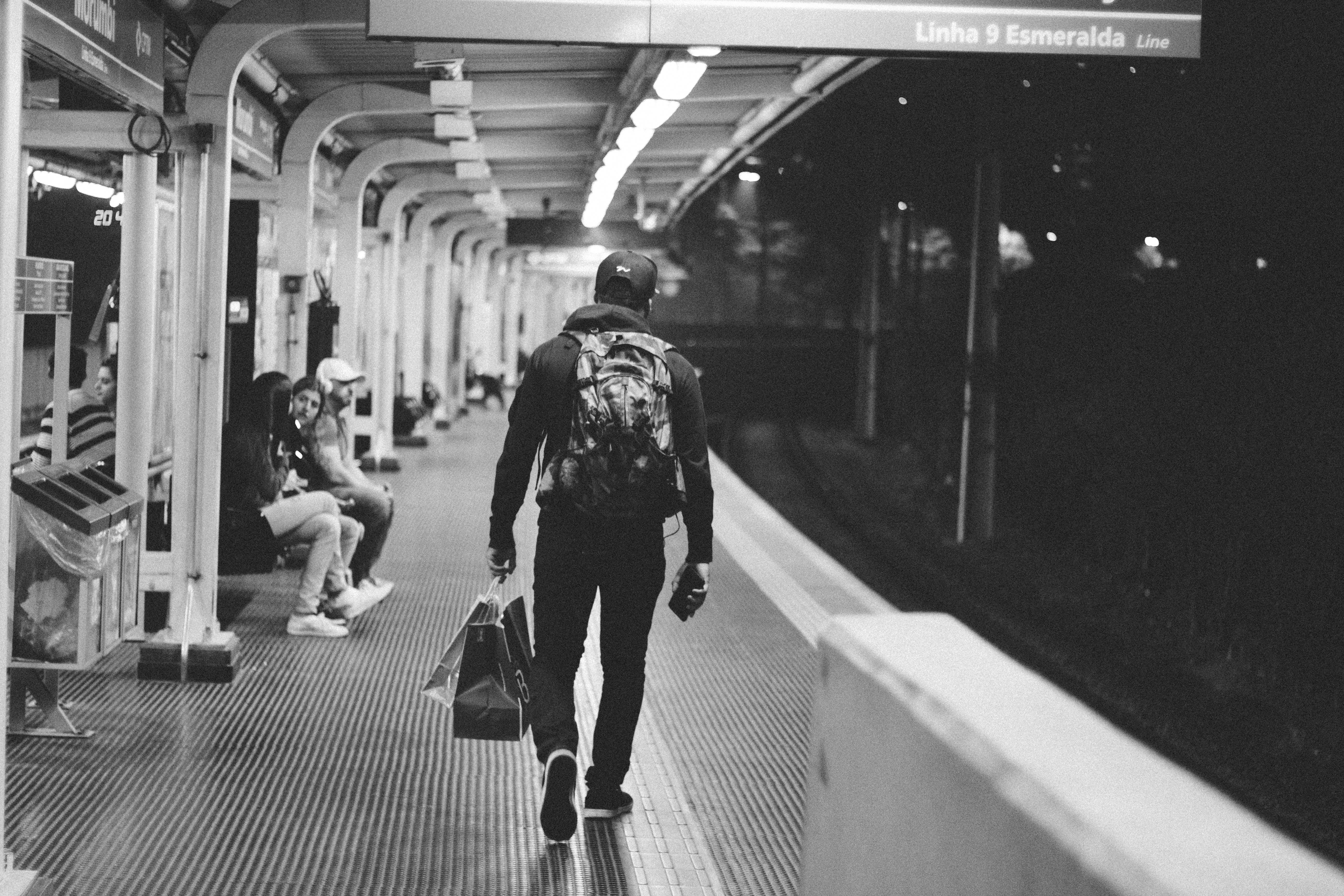 Grayscale Photography Man Walking on Hallway