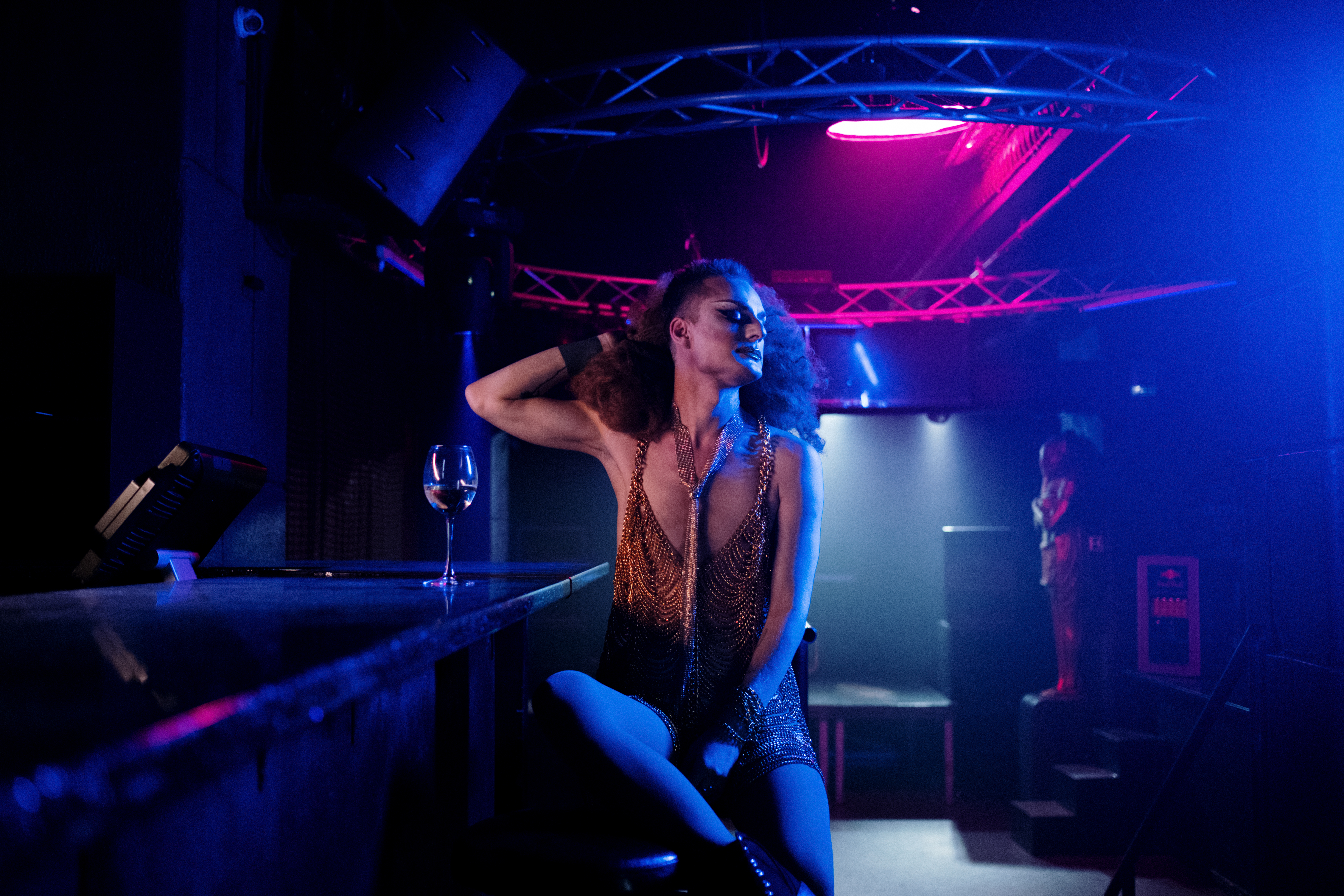 drag queen sitting at a bar