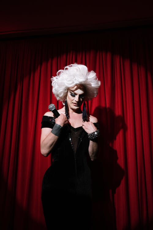Drag Queen Holding a Microphone on Stage