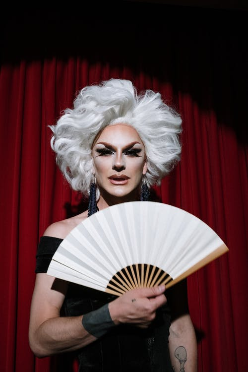 Drag Queen Holding a White Hand Fan