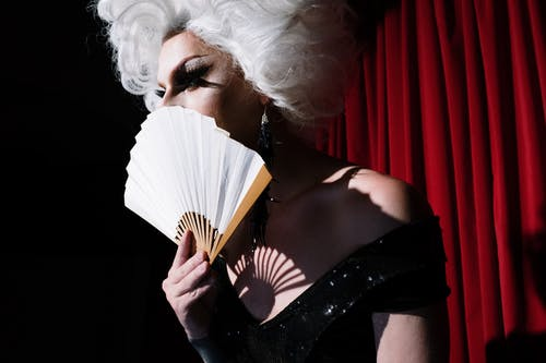 Drag Queen Holding White Hand Fan