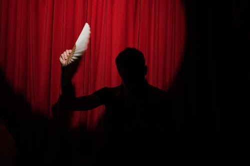 Silhouette of a Person Holding a Hand Fan on Stage