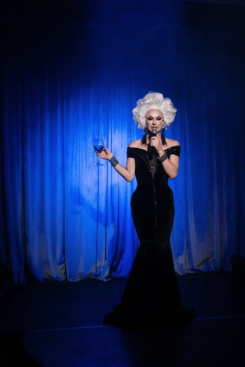 Drag Queen Holding a Microphone and a Wine Glass on Stage