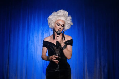 Drag Queen Holding a Microphone and a Glass of Wine on Stage