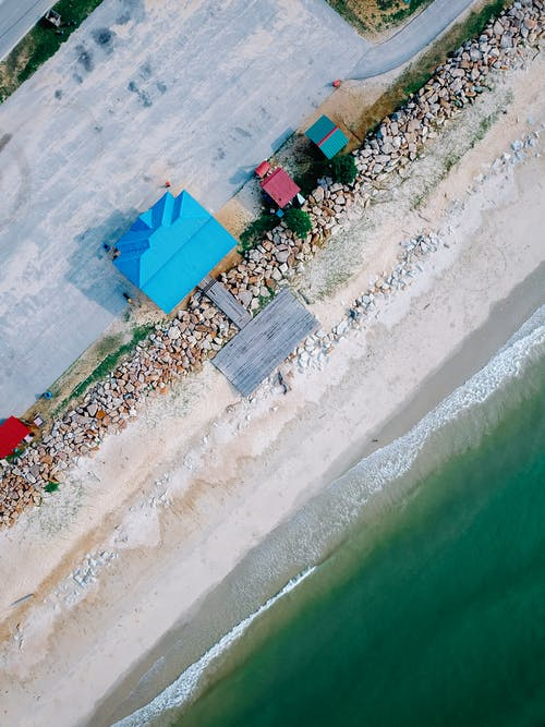 Drone view of small houses located near sandy beach of wavy ocean on sunny day