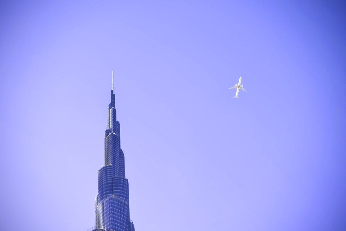 White Airplane Flying over Building